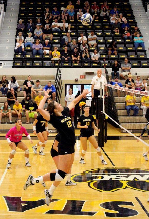 ELIZABETH GEBHARDT leaps tp spike the ball against Upper Iowa University last friday. Also pictured are Courtney VanGroningen, Alyssa Frauendorfer, and Michaela Mestl.