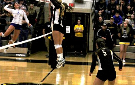 Two WSC volleyball players leap to block an incoming shot from Kearney in last Tuesday's game.