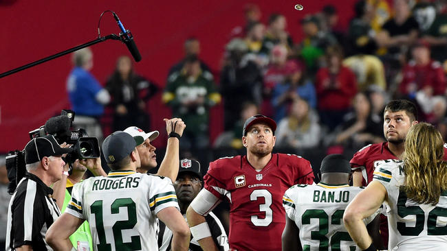 Aaron Rodgers and Carson Palmer watching the overtime coin toss.