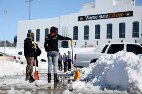 Students work on digging out their cars from the fast melting snow that fell last Wednesday into Thursday.
