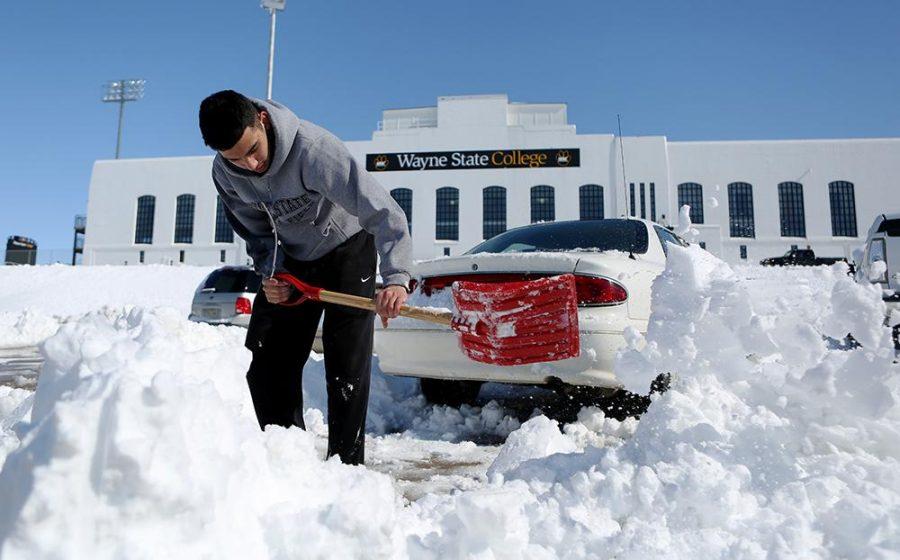 WSC student Allen Arauz scoops snow in the Rec Center parking Lot.