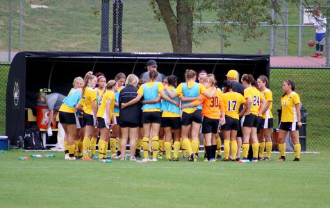 The WSC women's soccer team gathers together during a time out during Saturday's evening match against Northern State University. The Wildcats won the game in double overtime after trailing 2-0 in the first half. The home game was also senior day for the seniors on the team.