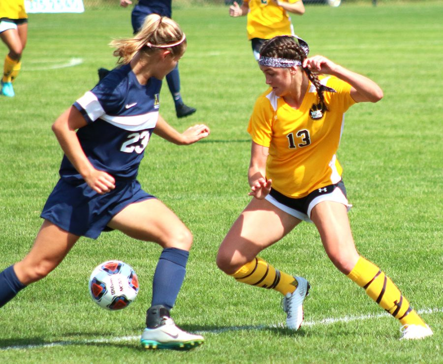 Madison Kemp faces off against Augustana player at Sundays game.