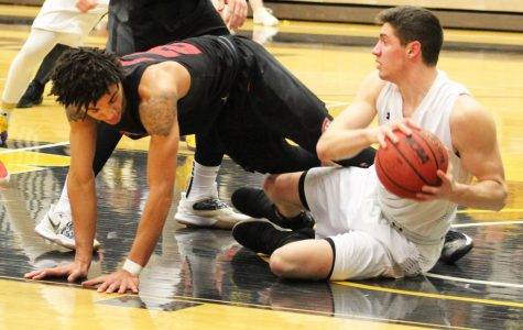 Sophomore Ben Detlinger scrambles on the ground for a loose ball against Saint Cloud opponent Friday night.