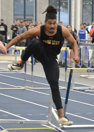 Robert Sullivan races over a hurdle while competing in the heptathlon, an event that combines seven different events including the 60 meter dash, 60 meter hurdles, 1,000 meter run, high jump, long jump, shot put, and pole vault.