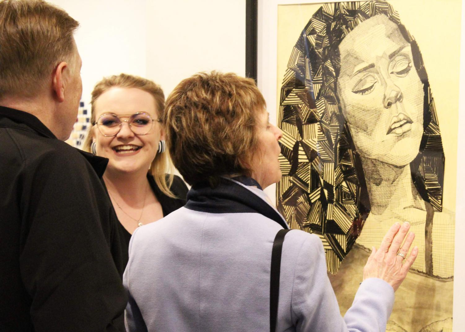 Senior Elley Coffin speaks to spectators during opening night of the senior art exhibit. Coffin is one of seven graduating art students displaying work in the show.