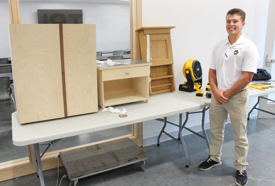 Wayne State College Student Derek Summers poses with his award-winning wood pieces. On top of being a student and competing with Skills USA, Summers owns his own business out of Norfolk called Summers Cabinetry.