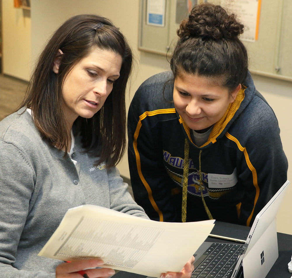 Wayne State College student Elena Rosberg (right) consults with Jessie Piper (left) at the Career Fair
