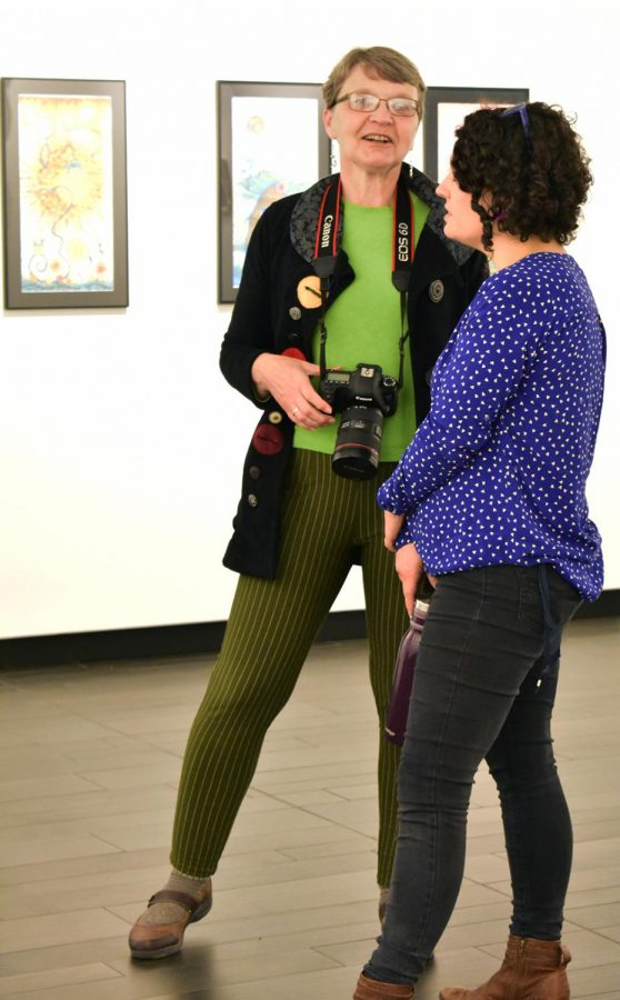 Pam Hanson and Meghan O'Connor pause their perusing of the Faculty Art Show to discuss a piece of work.